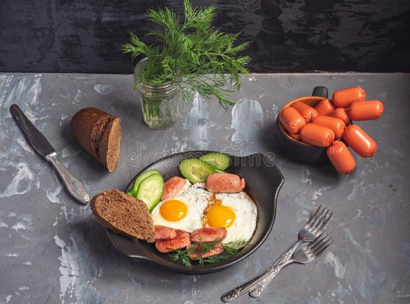 Śniadanie smażyć kiełbasy na czarnym ceramicznym talerzu i jajka W małym talerzu porcja kiełbasy dla następnego przygotowania fotografia stock