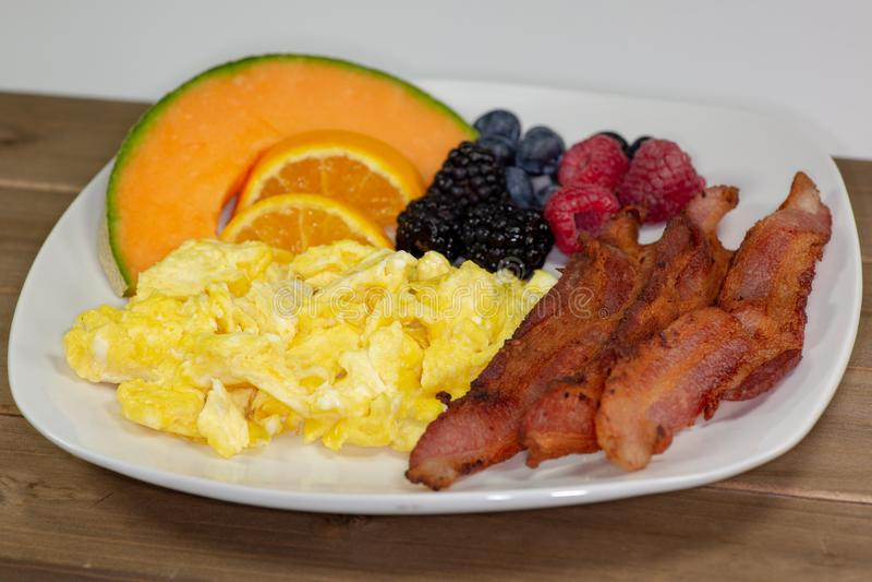 Śniadanie talerz bekon, cantaloup plasterek, pomarańczowi plasterki, czernicy, malinki i czarne jagody na kuchennym stole czeka t fotografia royalty free