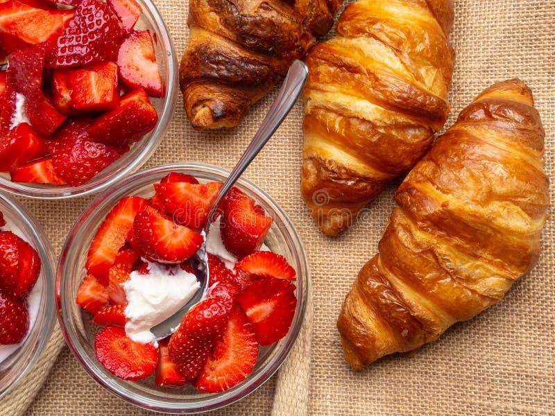 Śniadanie z świeżymi croissants, truskawka z śmietanką w szklanych pucharów tle zdjęcie royalty free