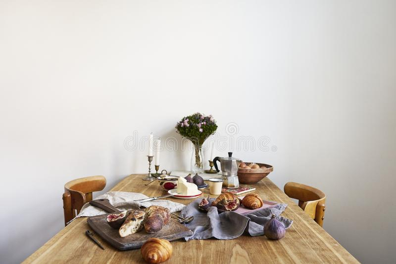 Śniadanie z croissants, figi, kawa na drewnianej desce nad nieociosanym drewnianym tłem, ceramics naczynia, grże kolory obraz stock