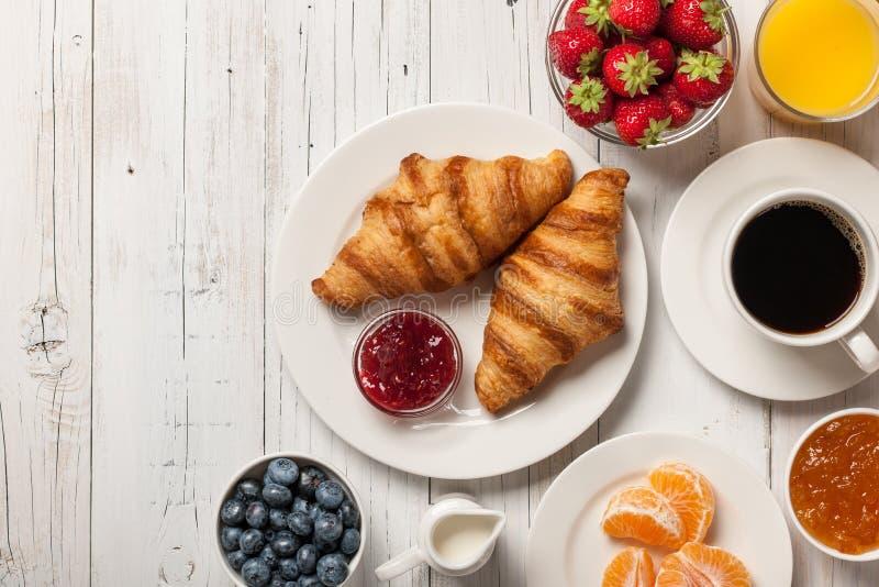 Śniadanie z croissants, kawą, dżemami i jagodami, fotografia stock