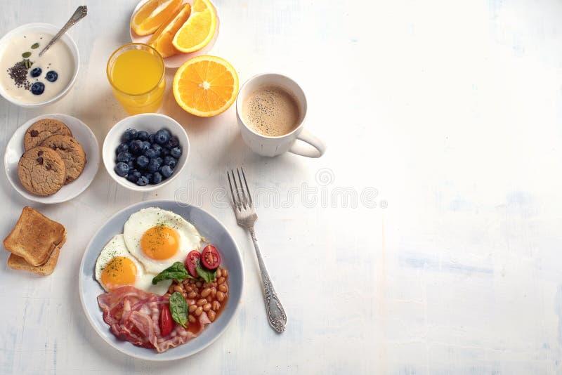 Śniadanie z jajkami, bekonem, sokiem pomarańczowym, jogurtem i grzanką smażącymi, zdjęcie royalty free