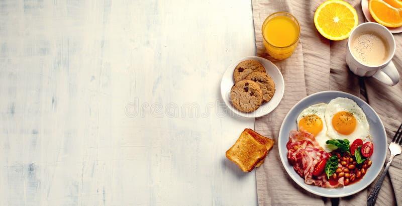 Śniadanie z jajkami, bekonem, sokiem pomarańczowym, jogurtem i grzanką smażącymi, fotografia stock