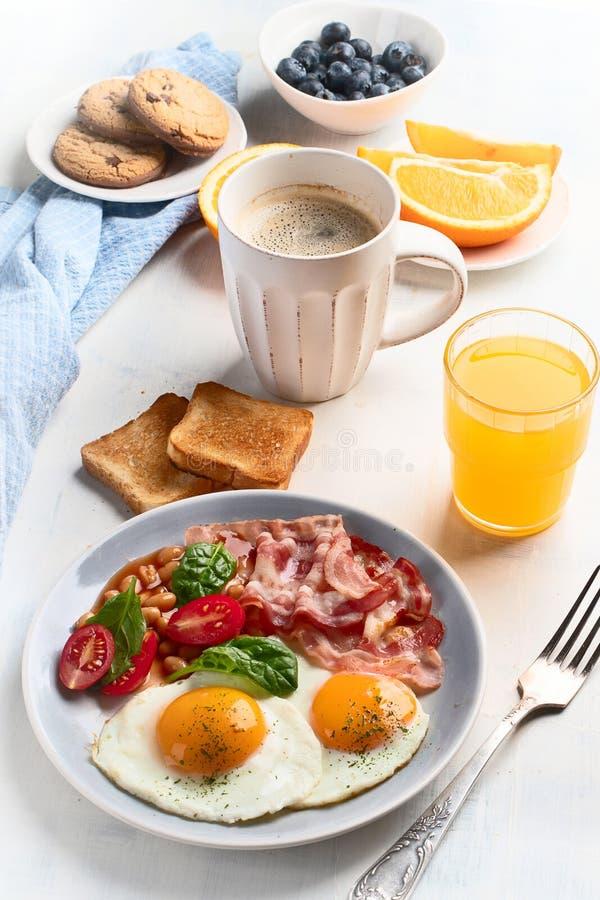Śniadanie z jajkami, bekonem, sokiem pomarańczowym, jogurtem i grzanką smażącymi, obrazy stock
