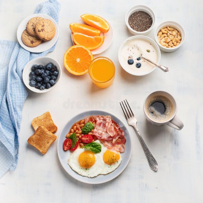 Śniadanie z jajkami, bekonem, sokiem pomarańczowym, jogurtem i grzanką smażącymi, zdjęcia royalty free