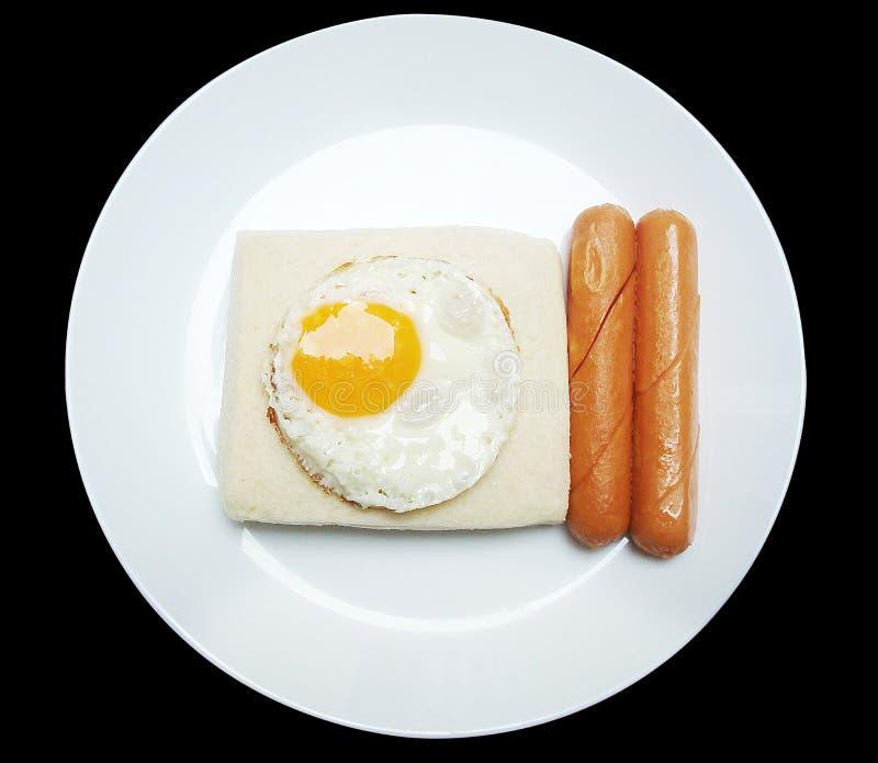 Śniadanie z jajkami smażył, chleb i kiełbasa na białym naczyniu obraz stock