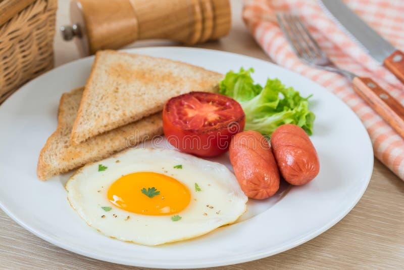 Śniadanie z jajkiem, grzanką, kiełbasą i warzywem na talerzu smażącymi, obrazy royalty free