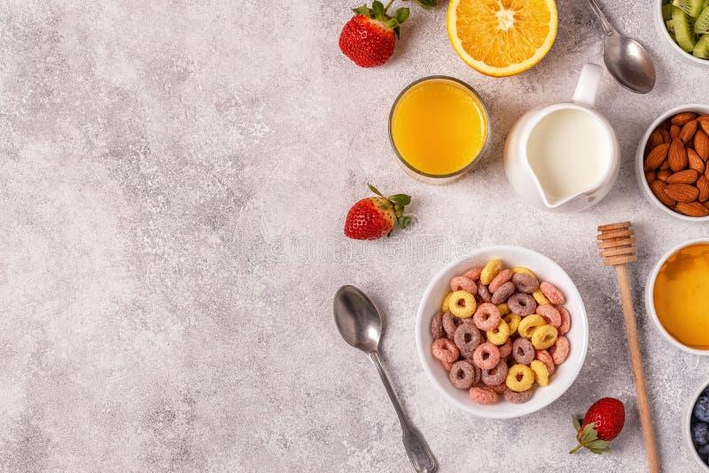 Śniadanie z kolorowym zbożem dzwoni, owoc, mleko, sok zdjęcie stock