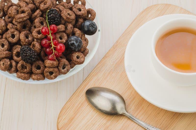 Śniadanie z płatkami, jagodami i filiżanką herbata, Odgórny widok, śniadanie z/płatkami, jagodami, łyżką i filiżanką herbata, Odg obraz stock