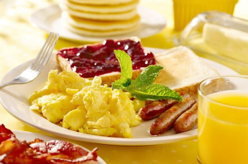 Śniadanie z rozdrapanymi jajkami, kiełbas połączeniami i t, obrazy royalty free