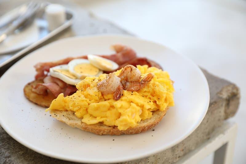 Śniadanie z rozdrapanymi jajkami, smażyć grule bekonowe i krewetkowe obraz royalty free