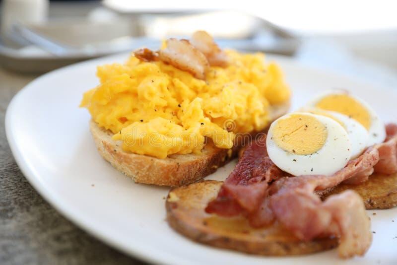 Śniadanie z rozdrapanymi jajkami, smażyć grule bekonowe i krewetkowe obraz stock