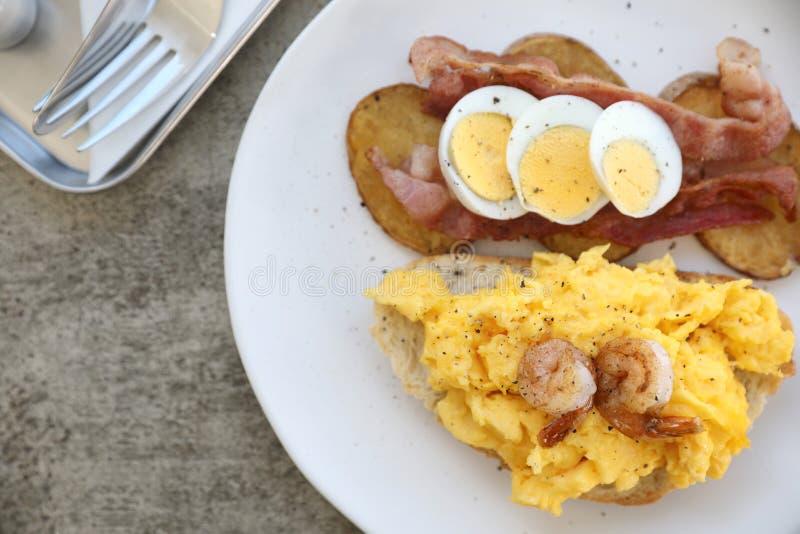 Śniadanie z rozdrapanymi jajkami, smażyć grule bekonowe i krewetkowe fotografia stock