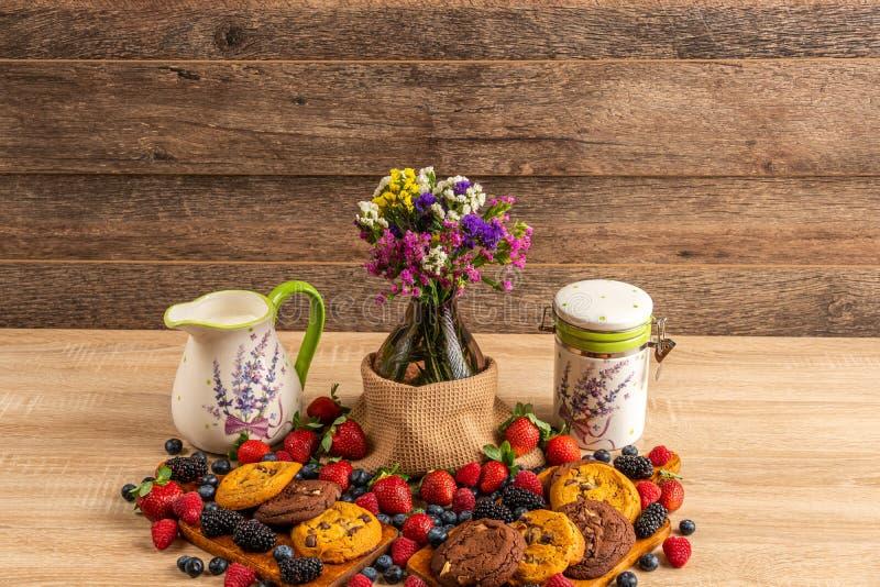 Śniadanio-lunch z dzikimi jagodami, czekoladowymi ciastkami i mlekiem, zdjęcie royalty free