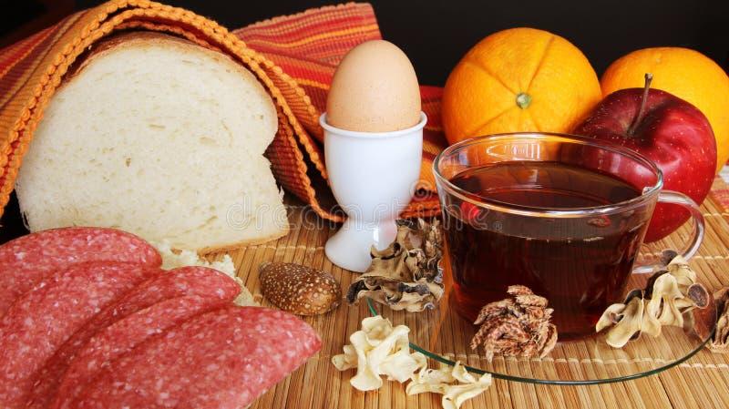Śniadaniowa czarna herbata z cytryną i prostym jedzeniem z dekoracją: chleb, masło, salami, pomarańcze, jabłko, wieprzowiny tende zdjęcie stock