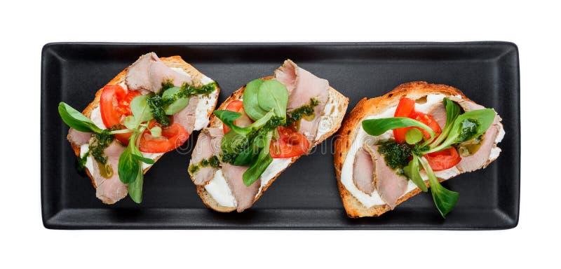 Śniadaniowa kanapka z baleronem, pomidorami, kremowym serem i szpinaka kumberlandem na czarnym talerzu odizolowywającym, zdjęcia royalty free