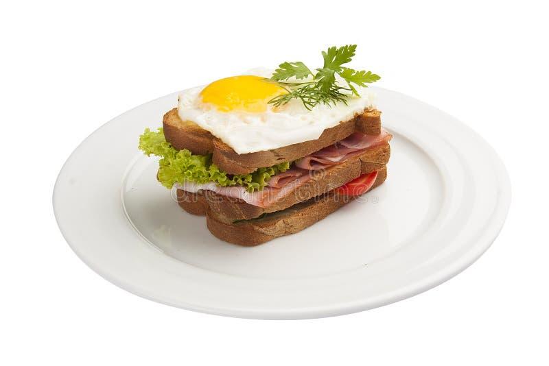 Śniadaniowa kanapka z jajkiem, baleronem i pomidorem, obraz royalty free