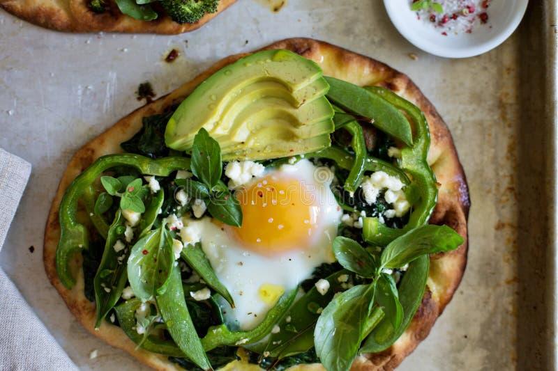 Śniadaniowa pizza z piec jajkiem i zieleniami obrazy stock
