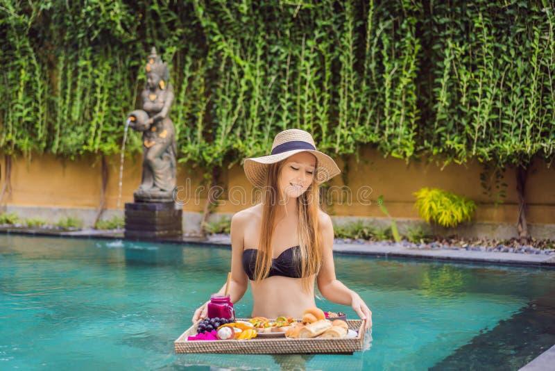 Śniadaniowa taca w basenie, spławowy śniadanie w luksusowym hotelu Dziewczyna relaksuje w basenie pije smoothies i zdjęcia stock