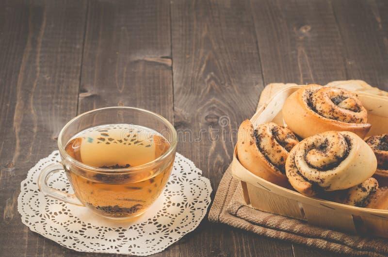 Śniadaniowe whith rolki z whith herbatą, Śniadaniowymi whith rolkami z filiżanki whith herbatą na zmroku drewnianym makową i szkl fotografia stock