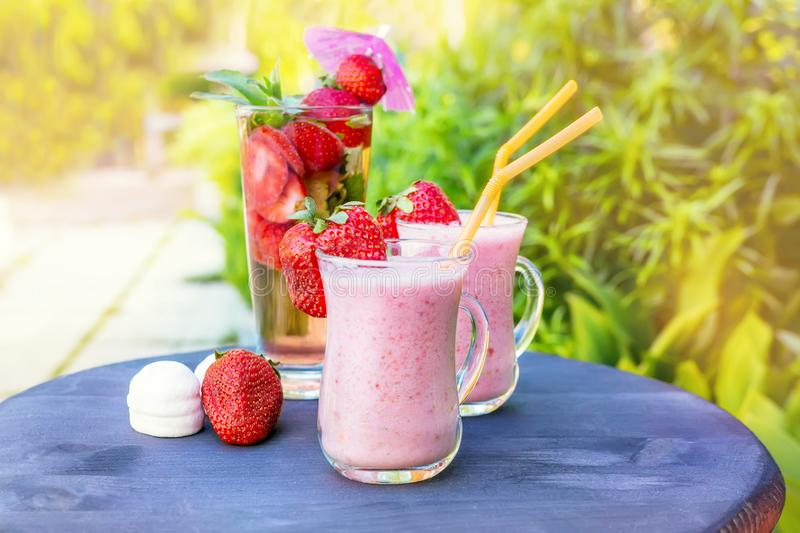 Śniadaniowego bananowego smoothie detox truskawkowy napój truskawki i mennica z marshmallows na zielonej rośliny tle fotografia royalty free