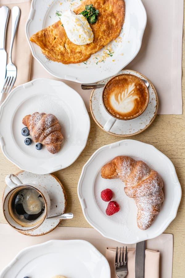 Śniadaniowi Croissants, kawa i wiele różni naczynia na stole w restauracji, Frittata - włoski omlet zdjęcie royalty free