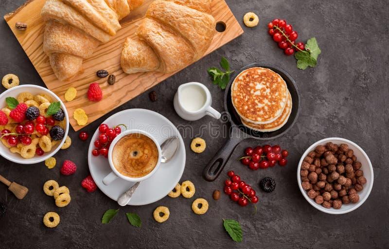 Śniadaniowi zboża, croissants, świeże jagody i filiżanka kawy, obraz stock