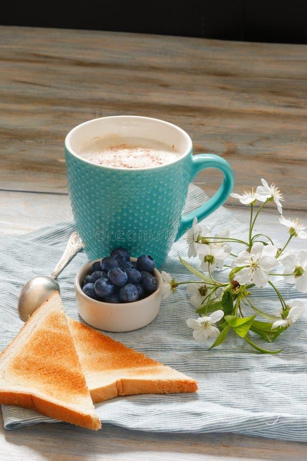 Śniadaniowy pomysł Filiżanka z kawą z czarnymi jagodami, czereśniowym okwitnięciem i grzanką na, bieliźnianej pielusze i drewnian obraz stock