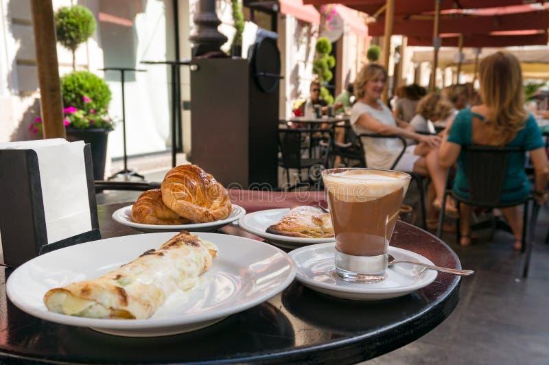 Śniadaniowy posiłek z kawą i croissants słuzyć przy plenerową restauracją w Włochy zdjęcia stock