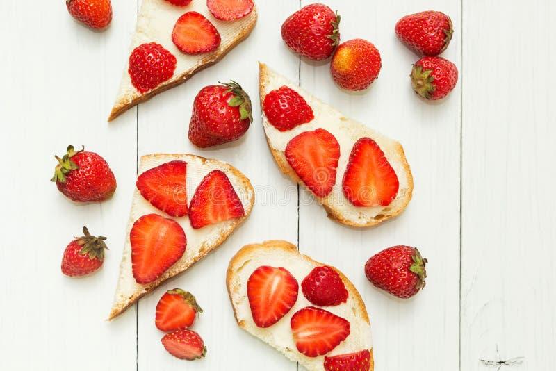 Śniadaniowy stół, całej banatki chleba grzanka z truskawką i masło na drewnianym stole, odgórny widok zdjęcie royalty free