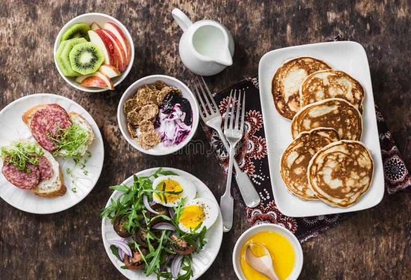 Śniadaniowy stół - grecki jogurt z całymi zbożowymi zbożami i jagodowym kumberlandem, bliny, arugula, czereśniowi pomidory, gotow obraz royalty free