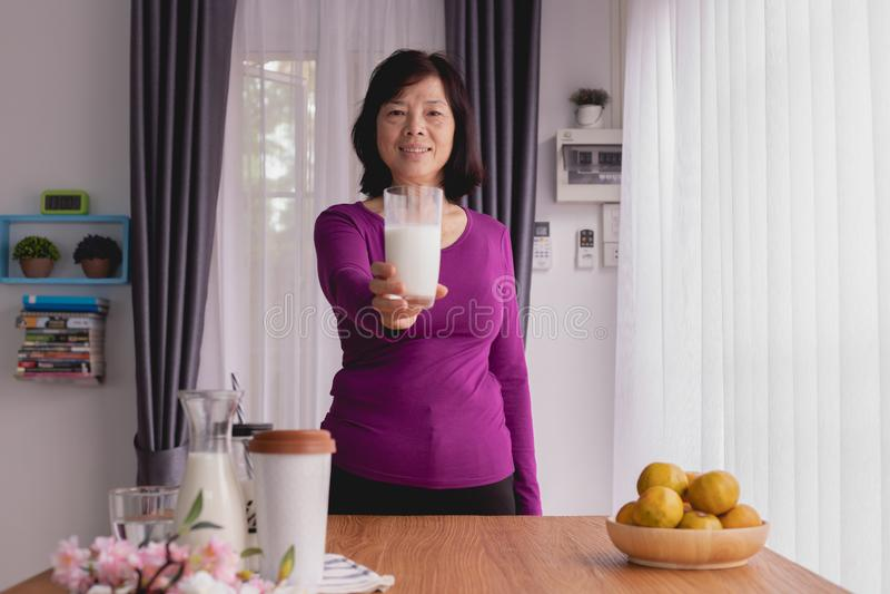 Śniadaniowy stół z Azjatyckim Starszym kobieta chwyta szkłem mleko w domu obrazy stock