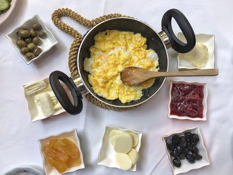 Śniadaniowy stół z rozdrapanym jajkiem, oliwkami, serem i dżemami, obrazy stock