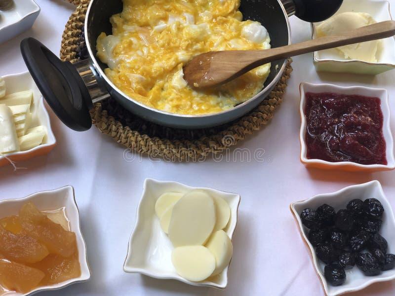 Śniadaniowy stół z rozdrapanym jajkiem, oliwkami, serem i dżemami, obraz stock