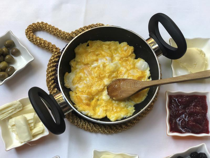 Śniadaniowy stół z rozdrapanym jajkiem, oliwkami, serem i dżemami, fotografia stock