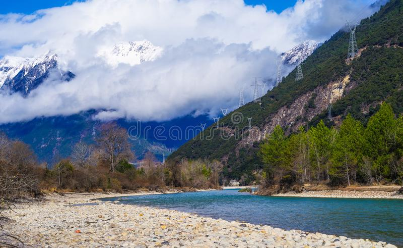 Śnieżna góra, jasny rzeki jar zielony krajobraz fotografia stock