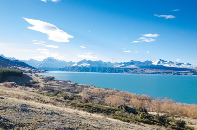 Śnieżna góra z błękitnym jeziora niebieskiego nieba i wody tłem przy Południową wyspą, Nowa Zelandia fotografia royalty free