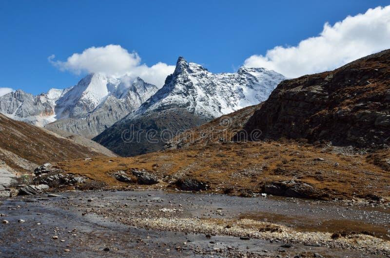 Śnieżna skalista góra z wysokogórskim w jesieni z jasnym niebem zdjęcie royalty free