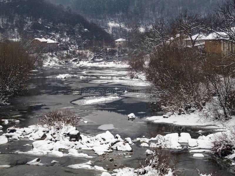 Śnieżna zimy wioska wynosił widok od mostu starzy riverbank domy i rzeka obrazy royalty free