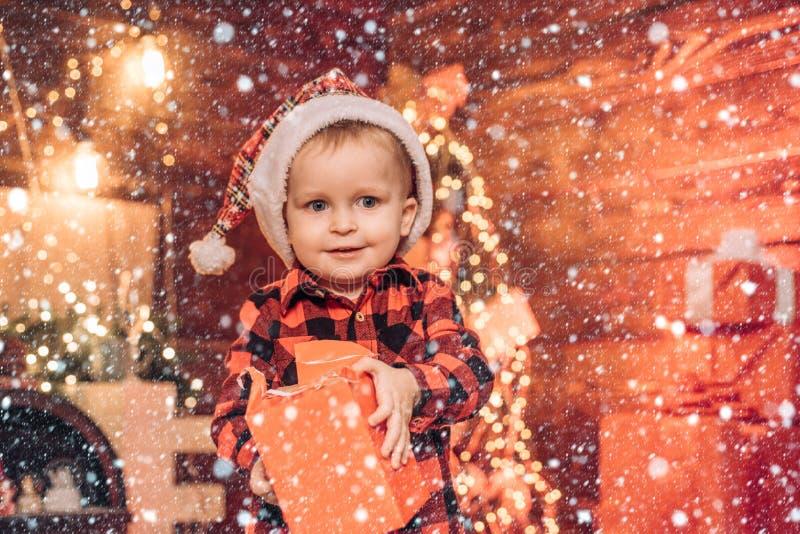 Śnieżne dzieci Szczęśliwe dziecko z pudełkiem na prezent świąteczny Niespodzianka Pole prezentowania Mały chłopiec w ciepłych ubr zdjęcie stock