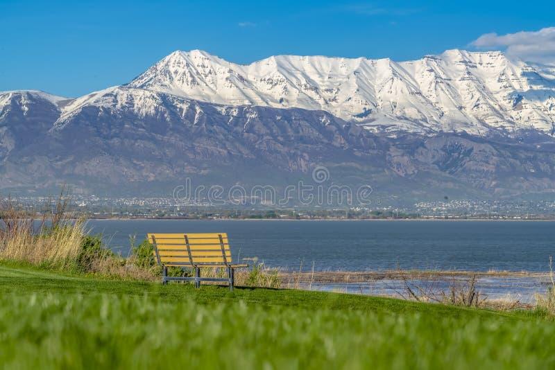 Śnieżny halny górować nad jeziorem i doliną pod niebieskim niebem na słonecznym dniu zdjęcie stock