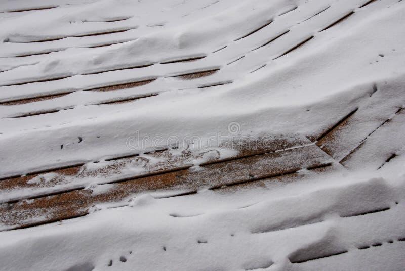 Śnieżny odsiew przez pęknięć w pokładzie obraz stock