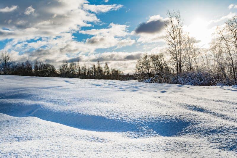 Śnieżny pole i las podczas zmierzchu jaskrawy słońce, niebieskie niebo z chmurami, zima krajobraz fotografia stock