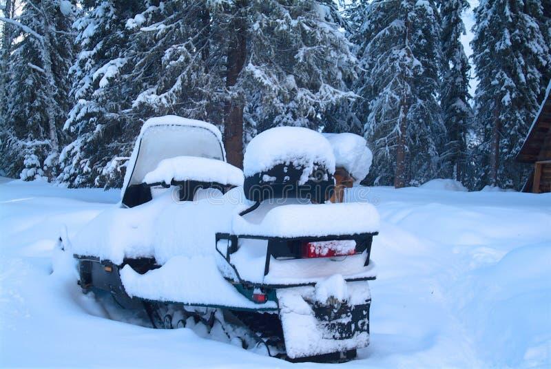 Śnieżny snowmobile blisko drewnianego domu w drewnach zdjęcie royalty free
