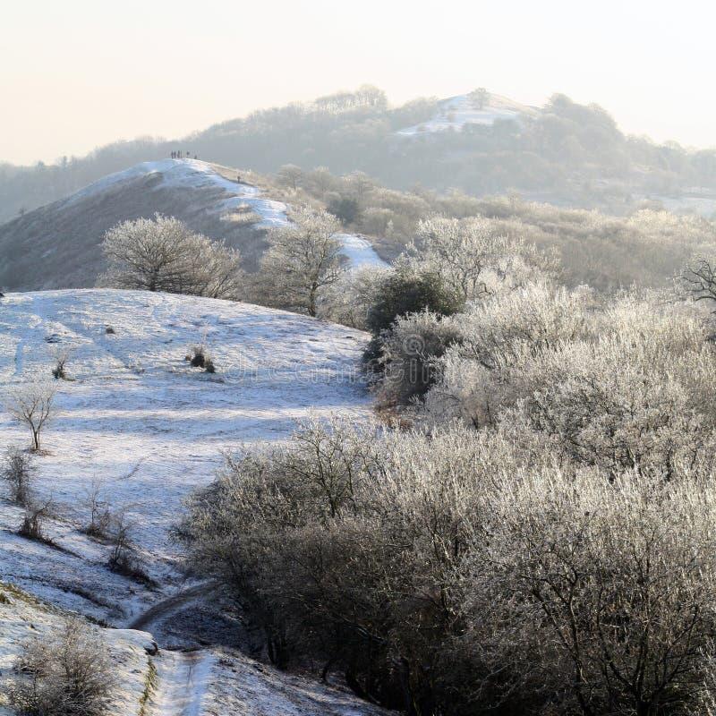 Śnieżny zima dzień na Malvern wzgórzach, patrzeje nad granią z grupa ludzi na górze jeden wzgórza w backgrou obrazy stock