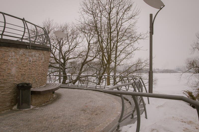 Śnieżyści drzewa i ławki w miasto parku Starszy mężczyzna w rekreacyjnym parku obrazy royalty free