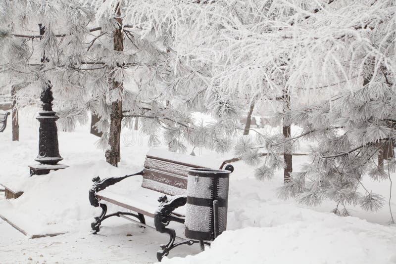 Śnieżysta ławka w miasto parku fotografia stock