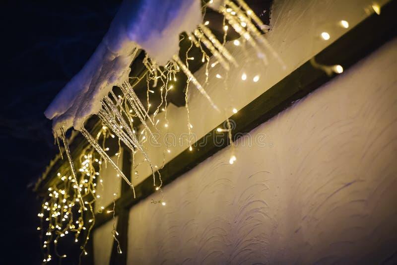 Śnieżysty dach dom dekorował z girlandą fotografia royalty free