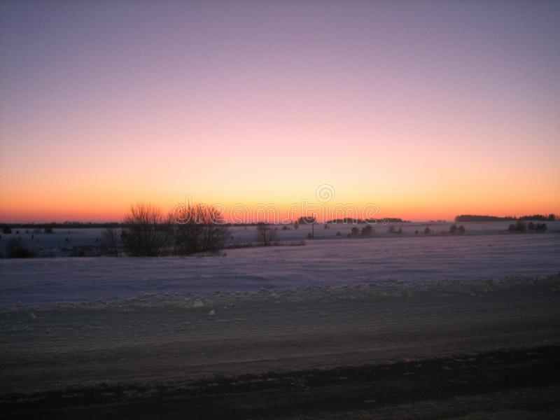 Śnieżysty pole wzdłuż drogi w zima wieczór przy zmierzchem obraz stock