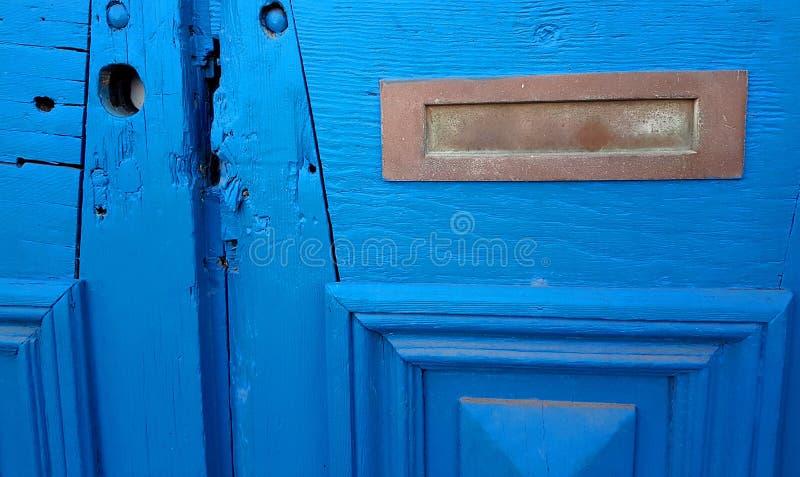 Śniedzi poczta Mosiężna szczelina w Zakłopotanym Błękitnym Drewnianym drzwi zdjęcie royalty free